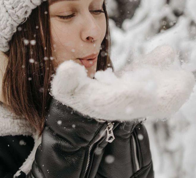 Eine verliebte Frau bläst ihre Handschuhe voller Schnee